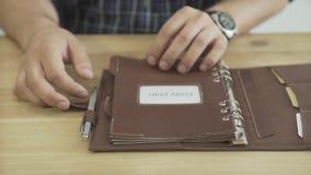 Slutet sköt upp av manhänder som öppnar elegant ljus - tidskrift för stadsplanerare för brunt block för läderanmärkningsbok dagli stock video