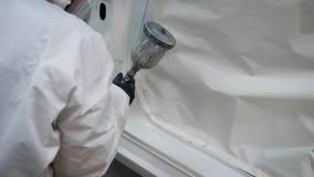 Slutet sköt upp av mannen som bär skyddande enhetliga målningsidokjolar av en bil i ett garage lager videofilmer
