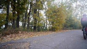 Slutet sköt upp av ung kvinna på en cykel i hösten parkerar arkivfilmer