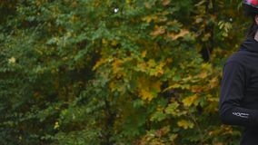 Slutet sköt upp av ung kvinna på en cykel i hösten parkerar långsam rörelse lager videofilmer