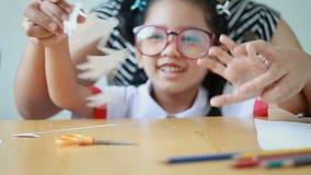 Slutet sköt upp den asiatiska lilla flickan i thailändsk dagisstudentlikformig och hennes modern som spelar snittet av form för v arkivfilmer