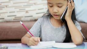 Slutet sköt upp den asiatiska lilla flickan som använder blyertspennan som gör läxa och samtal till smartphonen lager videofilmer