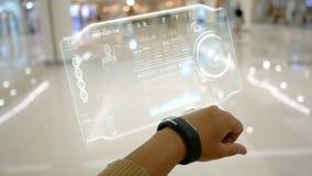 Slutet sköt upp händer av kvinnan som använder den smarta klockan med HUD användargränssnittet för futuristisk applikation för cy arkivfilmer
