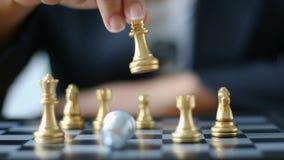 Slutet sköt upp handen av affärskvinnan som flyttar guld- schack för att besegra ett silverkonungschack på vit- och svartschackbr