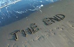 SLUTET som är skriftligt på stranden vid havet, medan vågen kommer Arkivfoto