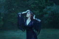 Slutet synar, flickadansen i måneljuset i den mörka smaragdskogen bara magi häxa demon bära en lång svart royaltyfria bilder