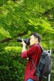 Slutet upp arbete för kamera för håll för Aisan kinesiskt manfotograf i natur sköt lönn arkivbilder