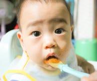 Slutet upp asiat behandla som ett barn pojken äter med en sked royaltyfri foto