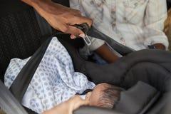 Slutet upp av att komma med för föräldrar som är nyfött, behandla som ett barn hem i bil royaltyfria foton