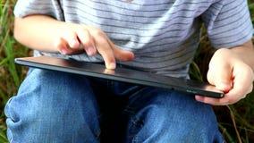 Slutet upp av barnets händer som spelar dataspelar på minnestavlaPC:n i, parkerar utomhus unge som använder minnestavladatorpeksk arkivfilmer