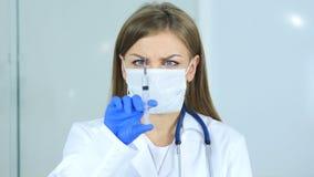 Slutet upp av den kvinnliga doktorn i hållande injektion för maskering, ordnar till för att injicera Arkivbilder