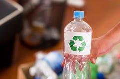 Slutet upp av en hand som rymmer en plast- flaska med ett utskrivavet tecken av återanvändning framme, återanvänder och kassaskåp Fotografering för Bildbyråer
