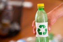Slutet upp av en hand som rymmer en plast- flaska med ett utskrivavet tecken av återanvändning framme, återanvänder och kassaskåp Royaltyfri Fotografi