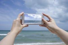 Slutet upp av kvinnans den hållande smartphonen för hand, mobil, ilar telefonen över det suddiga härliga blåa havet för att ta et Arkivfoton