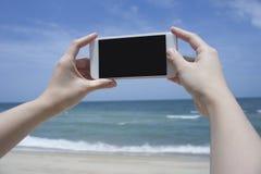 Slutet upp av kvinnans den hållande smartphonen för hand, mobil, ilar telefonen över det suddiga härliga blåa havet för att ta et Royaltyfri Bild