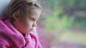 Slutet upp av lite den gulliga flickan i rosa badrock stirrar SAD ut ur ett fönster Sitta på fönsterfönsterbrädan stock video