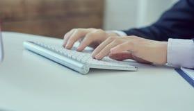 Slutet upp av mannen räcker maskinskrivning på tangentbordet för den skrivbords- datoren i regeringsställning Affär utbytesmarkna arkivbild