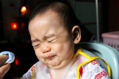 Slutet upp av olyckliga små sju månader gammal son ser in att igenom den plast- haklappen som skriker och gråter i stol för behan arkivbilder