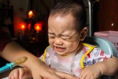 Slutet upp av olyckliga små sju månader gammal son ser in att igenom den plast- haklappen som skriker och gråter i stol för behan arkivfoto