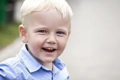 Slutet upp, blondinen behandla som ett barn pojken Fotografering för Bildbyråer