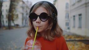 Slutet upp den tonåriga nätta hipsteren lyssnar musik i hörlurar, drinkmilkshake från en plast- kopp som ler och går gatan arkivfilmer