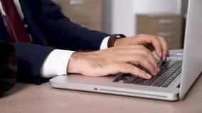 Slutet upp dockaglidbanaaffärsman skriver på bärbar datortangentbordet arkivfilmer