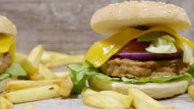 Slutet upp dockaskott på aptitretande hamburgare med fransman steker på träbakgrund lager videofilmer