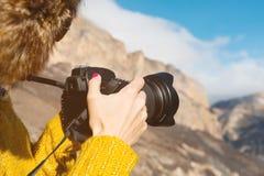 Slutet upp a-flickafotograf i en pälshatt och en gul tröja i bergen tar bilder på hennes digitala kamera Arkivfoto