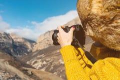 Slutet upp a-flickafotograf i en pälshatt och en gul tröja i bergen tar bilder på hennes digitala kamera Royaltyfri Bild