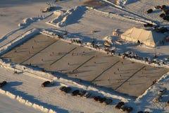 Slutet upp flyg- silvermin skidar isbanan för invitaionalhockeyturnering Royaltyfria Foton
