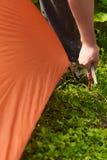 Slutet upp händer för man` s klibbar en pinne in i jordningen, medan ställa in - upp ett tält i skogen Royaltyfri Bild