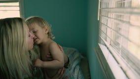 Slutet upp härlig moder för stående rymmer en behandla som ett barnson, stort fönster i bakgrunden lager videofilmer