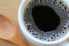 Slutet upp i svart kaffe är i en vit rånar på en brun träflo Arkivfoton