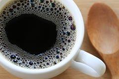 Slutet upp i svart kaffe är i en vit rånar på en brun träflo Arkivfoto