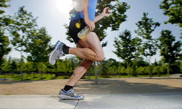 Slutet upp idrotts- ben av spring för den unga mannen i stad parkerar med träd på livsstil för praktiserande sport för sommarutbi Arkivfoto