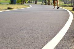 Slutet upp jordyttersida av staden parkerar trottoar med varmt ljus i aftonen och gjorde suddig en man som joggar på en väg arkivbilder