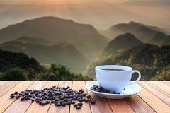 Slutet upp koppen för vitt kaffe och kaffebönor på den wood tabellen och tävlar Arkivfoto