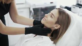 Slutet upp kosmetologhänder undersöker och trycker på patientens framsida stock video