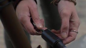 Slutet upp kvinna räcker genom att använda tangenten för att stänga anti-stöldlåset på cykelparkering arkivfilmer
