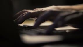 Slutet upp kvinna räcker tangentbordet för maskinskrivningtextanteckningsboken i mörk inre lager videofilmer