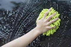 Slutet upp kvinnahandhåll en borste som tvättar sig över den svarta bilen, kvinna kan tvätta begreppet, kvinna kan göra begrepp Royaltyfria Foton