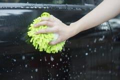 Slutet upp kvinnahandhåll en borste som tvättar sig över den svarta bilen, kvinna kan tvätta begreppet, kvinna kan göra begrepp Royaltyfri Bild