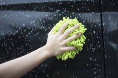 Slutet upp kvinnahandhåll en borste som tvättar sig över den svarta bilen, kvinna kan tvätta begreppet, kvinna kan göra begrepp Arkivfoton