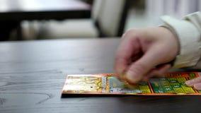 Slutet upp kvinnan som skrapar lottsedeln, kallade kontant tryckvåg lager videofilmer