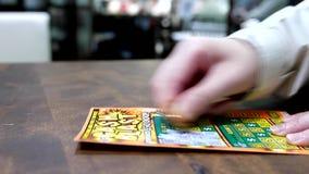 Slutet upp kvinnan som skrapar lottsedeln, kallade kontant tryckvåg inom shoppinggalleria stock video