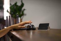 Slutet upp kvinnor kallar hotellmottagande på räknareskrivbordet med fingret royaltyfri fotografi