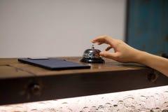 Slutet upp kvinnor kallar hotellmottagande på räknareskrivbordet med fingret arkivfoto
