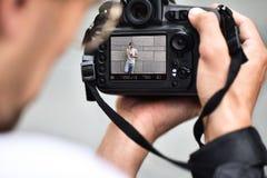 Slutet upp manliga händer rymmer den yrkesmässiga kameran och gör ett foto royaltyfri foto