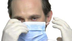 Slutet upp mogen doktor sätter på medicinsk maskering stock video