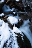 Slutet upp på bergbäckfloden som between flödar, vaggar dolt med snö royaltyfria bilder